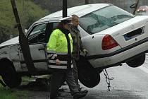 Policie asistuje při nakládání havarovaného mercedesu na silnici I/13 mezi Mostem a Litvínovem.