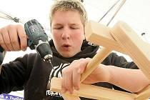 Mladý učeň pracuje se dřevem.