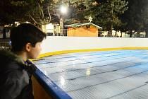 Zvědavý kluk sleduje první led na kluzišti u radnice.