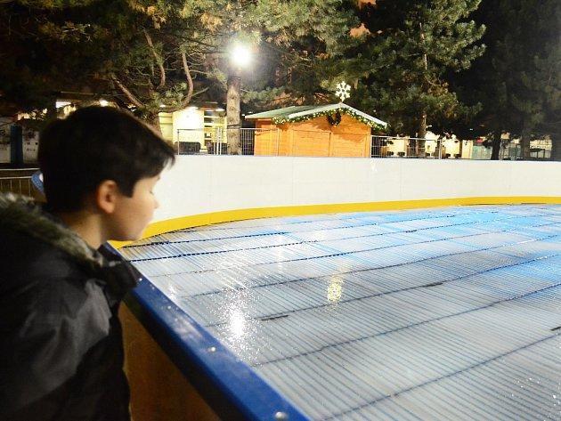 Zvědavý kluk sleduje první led na kluzišti uradnice.