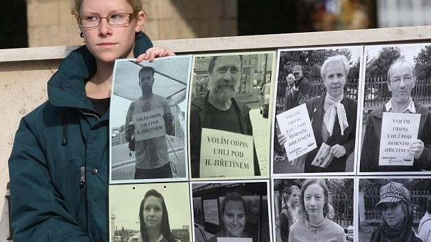 Aktivistka drží před mosteckým magistrátem fotografie lidí, kteří se účastní fotopetice proti těžbě uhlí pod Horním Jiřetíněm.