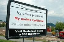 Billboard z dílny Jiřího Zelenky se tváří jako volební kampaň Sdružení Mostečané Mostu. Cílem je toto sdružení zostudit.