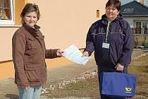 Obyvatelka Andrea Sirůčková přebírá formuláře k nadcházejícímu sčítání lidu od své sčítací komisařky Marcely Sakovičové, pracovnice České pošty. Náročnou celostátní akci za 2,5 miliardy korun pořádá Český statistický úřad.