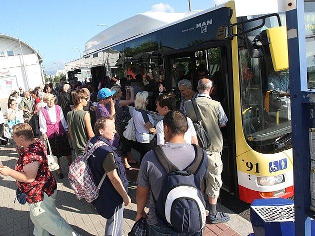 Lidé nastupují do autobusu na zastávce u nemocnice. Je na mostě, který teď město zavře, zastávka se přesune.