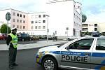 Policista hlídá vjezd na parkoviště k mosteckému finančnímu úřadu. Anonym tam nahlásil bombu.