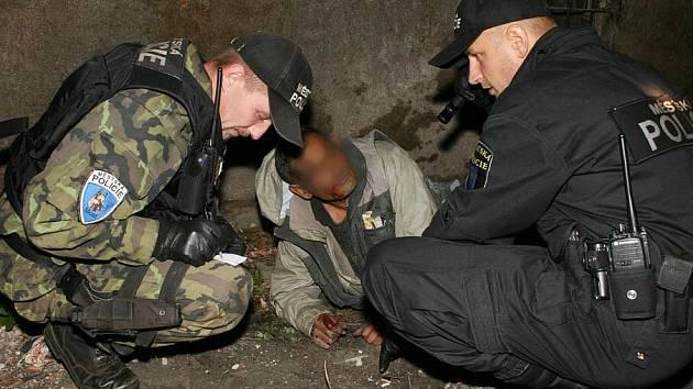 Strážníci komunikují s mužem, který v opilosti vypadl z okna.