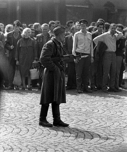 Voják pochodující poblíž divadla má sice ruce v kapse, zároveň má ale připravený samopal s bodákem.