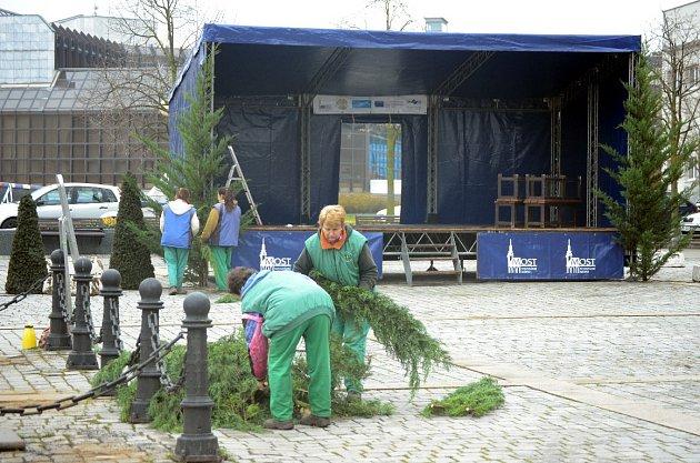 Mezi budovou mostecké radnice a hotelem vzniká veřejné venkovní ledové kluziště, na sousedním 1.náměstí instalují Vánoční trh a zdobí 40let starou vánoční jedli, dar od občana.