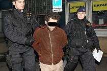 Policisté odvádějí muže, který se obnažoval a odhaloval své přirození v nádražní hale v Mostě.