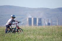 Malý cyklista si vyjel po planině u zbytkové jámy dolu Ležáky, ze kterého chce stát udělat jezero. V pozadí je Chemopetrol.