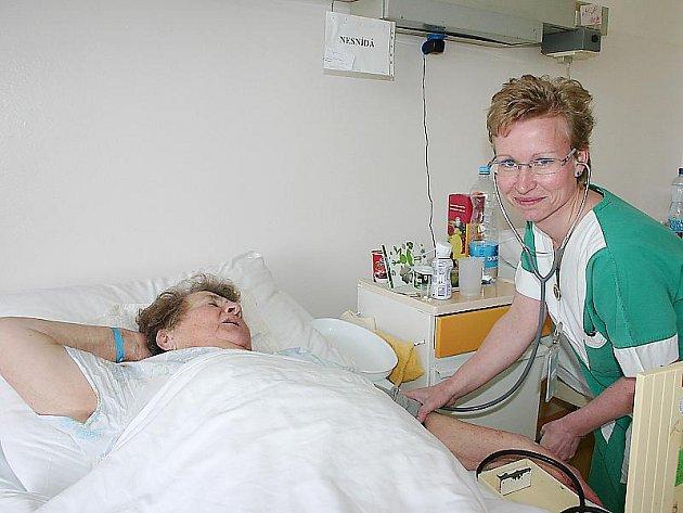 Všeobecná sestra z interního oddělení v nemocnici v Mostě Renáta Kalčíková měří pacientce krevní tlak. Zdravotních sester společnost Krajská zdravotní ve svých pěti nemocnicích zaměstnává celkem 2800.