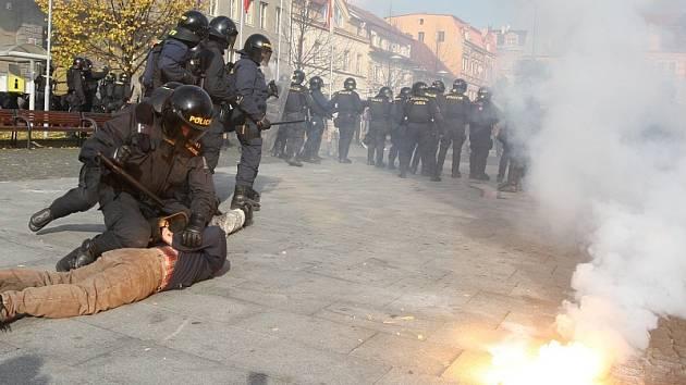 Policisté zadržují jednoho z účastníků nepovolené demonstrace.