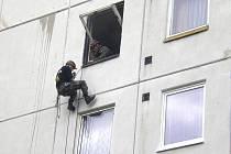 Strážník slaňuje z panelového domu.