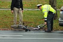 Policista zvedá kolo, které si přišel vyzvednout blízký cyklisty.