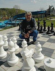 Správce koupaliště Ressl stojí na obří šachovnici, v pozadí je nový bazén plný atrakcí.