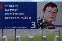 Hana Jeníčková čelí útoku neznámého recesisty. Toto je billboard u hlavní pošty, kde má plochu její rival Jiří Zelenka. Foceno v pátek večer. Pokusí se někdo obří plakát zničit?
