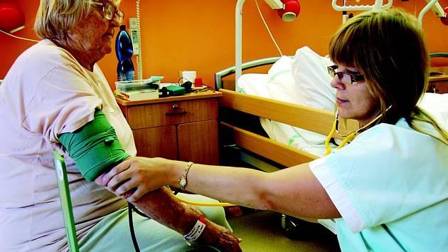 """Zdravotní sestra Jana Kousková měří tlak 88leté Miroslavě Kotěborské v Nemocnici následné péče v Mostě na Zahražanech. """"Jsem tu moc spokojená,"""" říká pacientka. Patří k těm, které si přejí, aby malá nemocnice fungovala beze změn jako dosud."""