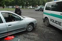 Policista si v pátek 11. července v 6 hodin ráno prohlíží poškozené a vykradené auto na okraji parkoviště naproti Penny v centru Mostu.