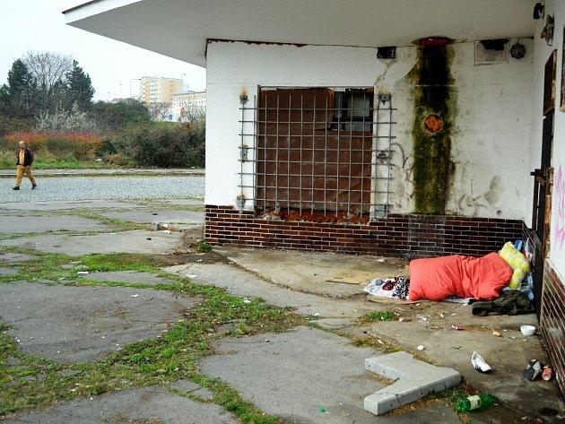 Bezdomovec spí pod peřinou na bývalém autobusovém nádraží v Mostě.