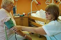 """Zdravotní sestra Jana Kousková měří tlak Miroslavě Kotěborské v Nemocnici následné péče v Mostě na Zahražanech. """"Jsem tu moc spokojená,"""" řekla pacientka, která si také přála, aby malá nemocnice fungovala beze změn jako dosud. Snímek je z loňského září."""