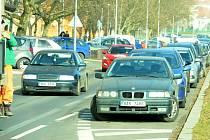 Popelář sleduje situaci na zúžené silnici u Stovky, z níž mají brzy zmizet parkující auta (vpravo).