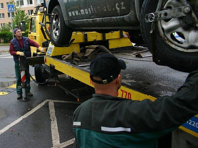 Odtahová služba nakládá vozidlo, které překáželo v čištění ulice.