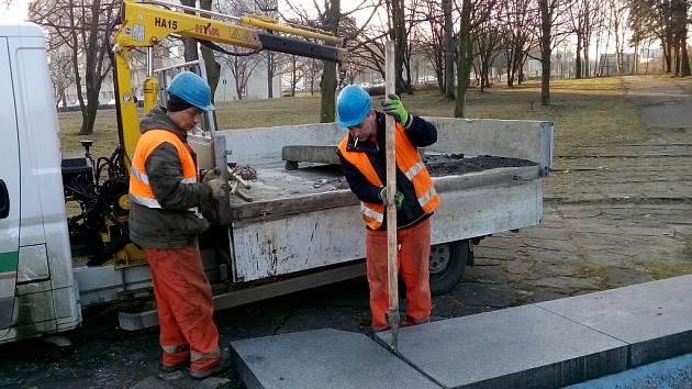 Pracovníci technických služeb nakládají a odvážejí rozbité žulové kvádry z okrajů bazénů.
