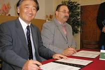 Šéf firmy Koito Czech Takao Yamanashi a ředitel Střední školy technické v Mostě Jiří Škrábal podepisují smlouvu o spolupráci.