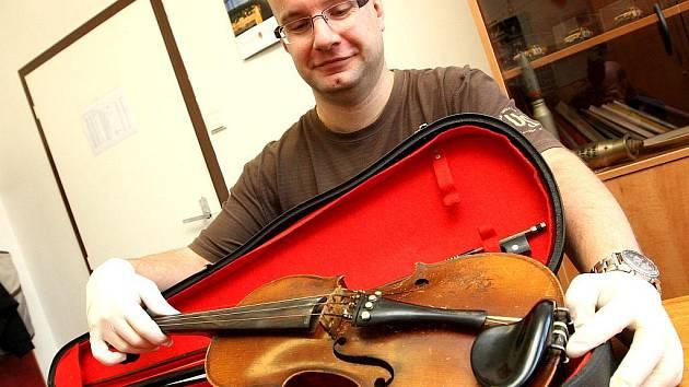 Kriminalista mostecké policie Radek Švarc kontroluje zabavené drahé housle, které pocházejí z lupu v jednom z vykradených bytů. policie poachatele zadržela a lup mu zabavila.