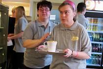 Zaměstnankyně kavárny míří za hosty. Sociální pracovnice jí ještě udílí pokyny.
