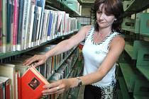 Knihovnice litvínovské knihovny Hana Polívková se probírá ve sklepním skladu regály se zatím nevyhozenými knížkami, které zasáhla tekoucí voda z prasklé hadičky u umyvadla.