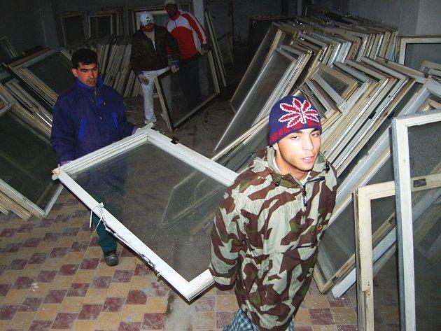 Zaměstnanci sdružení Dům romské kultury odnášejí vybraná stará okna, která v Mostě firmy vyhazují. V Chanově jsou ale užitečná.