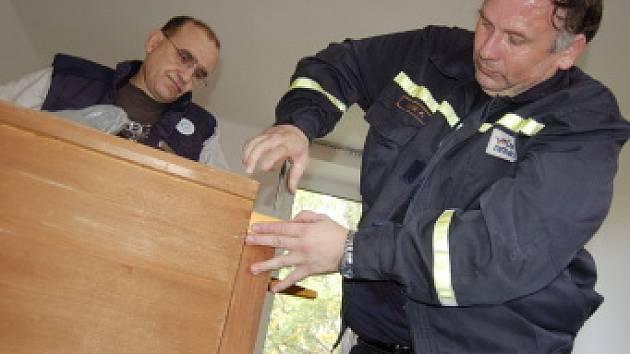 Operátor František Voleník opravuje skříň v pokoji azylového domu. Pomáhá mu mluvčí České rafinérské Aleš Soukup.