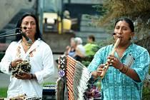 Pouliční koncert v centru Mostu. Lidé házejí umělcům mince do košíku.