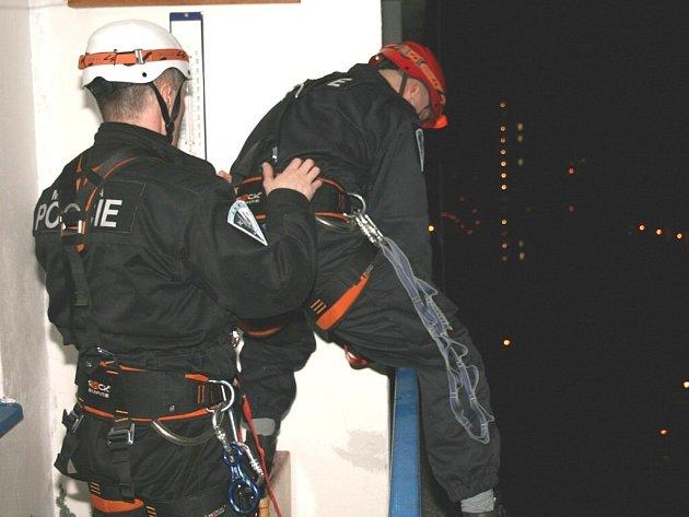 Strážníci lezou přes balkony v devátém patře do bytu ženy, která spáchala sebevraždu.