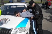 Strážník zadržuje podezřelého z loupeží.