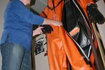 Ředitelka mosteckého muzea ukazuje hasičský oblek.