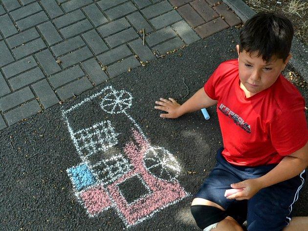 Děti malovaly na chodník před sportovní halou.