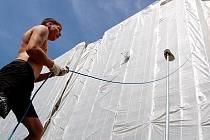 Stavební dělník zvedá na kladce kbelík s materiálem při rekonstrukci panelového domu na Zahražanech v Mostě. Velkorysý dotační program Zelená úsporám neřeší zateplení paneláků. Podpora je možná sice z jiných, ale méně štědrých dotačních titulů.