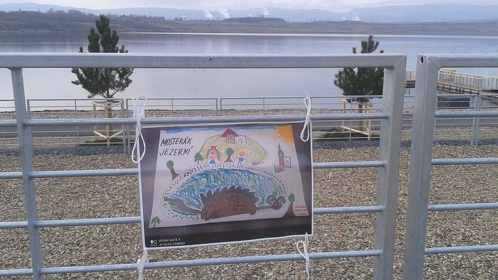 """Výstava obrázků dětí """"Po stopách jezerní příšery"""" na pláži jezera Most."""