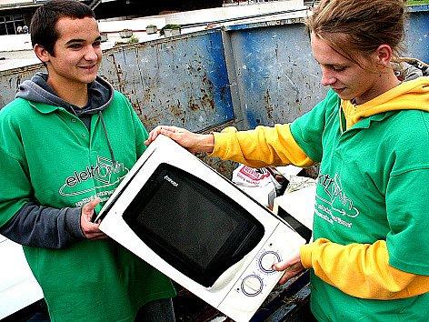 Martin Horák a Jan Rudolf ukládají do kontejneru mikrovlnnou troubu, kterou ve středu přinesl na náměstí jeden z Mostečanů.