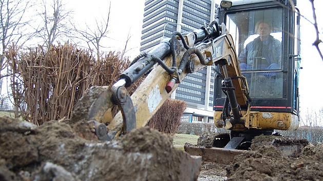 Miloslav Münfeld, řidič malého bagru značky CAT, zasypává jámu v centru Mostu. Pravě pro tyto a další speciální stroje bude nová továrna u Mostu vyrábět filtry. Stavebnictví zatím hospodářské recesi odolává.