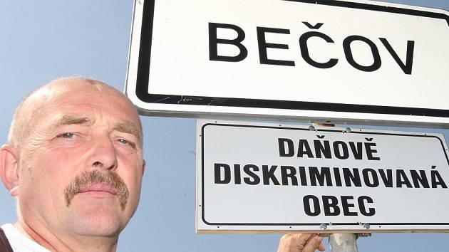 Starosta Bečova Václav Turnovský s cedulí, která poukazuje na daňovou diskriminaci malé obce.