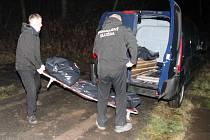 Pracovníci pohřební služby odnášejí tělo mrtvého muže