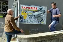 Karel Paťava (vpravo) připevňuje nový bilboard na budovu bývalého mosteckého krematoria
