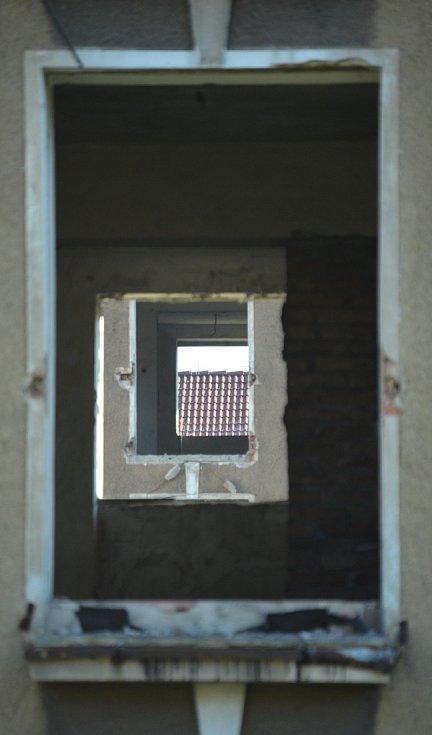 """Zóna 2B u bývalých kasáren v Mostě. Průhled na opravený dům přes dva """"průsvitné"""" vybydlené domy."""