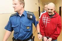 Obžalovaného Josefa Berchina v poutech přivádí do jednací síně mosteckého soudu justiční a vězeňská stráž. Čelí obžalobě z násilí proti ženě.