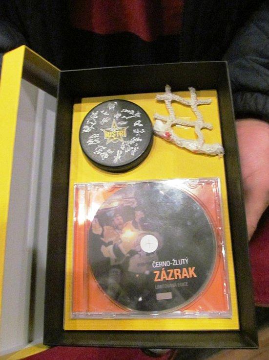 """Je to zatím """"pracovní"""" verze, ale zhruba takto bude vypadat obsah krabičky s chystaným DVD. Obsahovat bude kousek sítě z branky a puk s podpisy všech hráčů."""