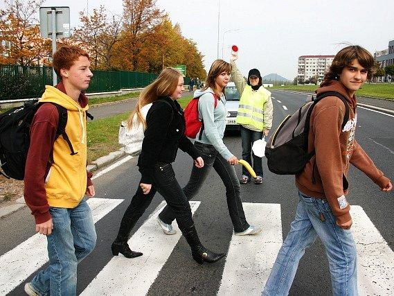 Míla Brožová zastavuje auta, aby mohli žáci 14. základní školy bezpečně přejít přes přechod.
