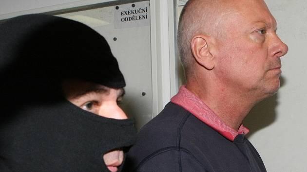Září 2012. Policista v kukle vede Pavla Koudu po chodbě krajského soudu, který tehdy poslal politika do vazby.
